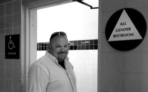 Principal Hewitson in front of the gender neutral restroom signage.
