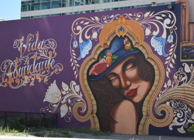 "The large purple mural that is painted on the wall of the Hotel De Anza, which says, ""Vida Abundante"", or ""abundant life"", as seen from the corner of Almaden Blvd. And West Santa Clara Street in San Jose, CA. Photo Credit: Estephany Haro"